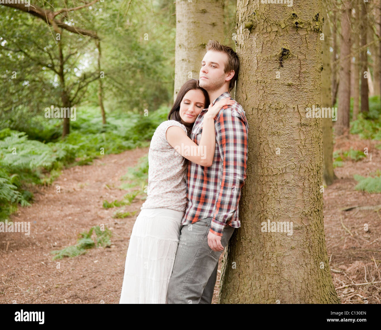 portrait of young couple in forest - Stock Image
