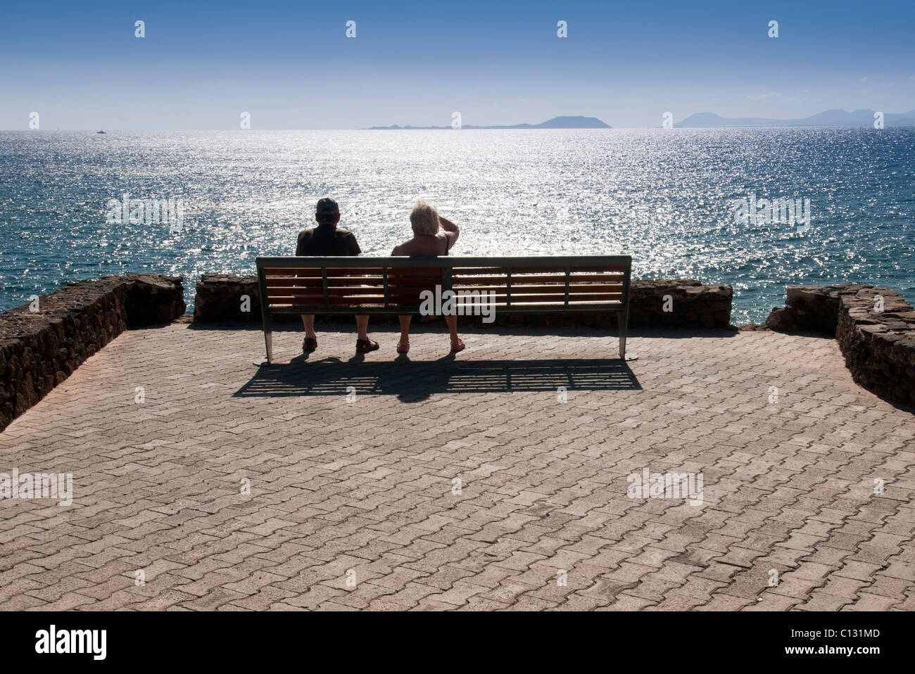 couple sitting on a bench enjoying the view out to sea in Lanzarote - Stock Image