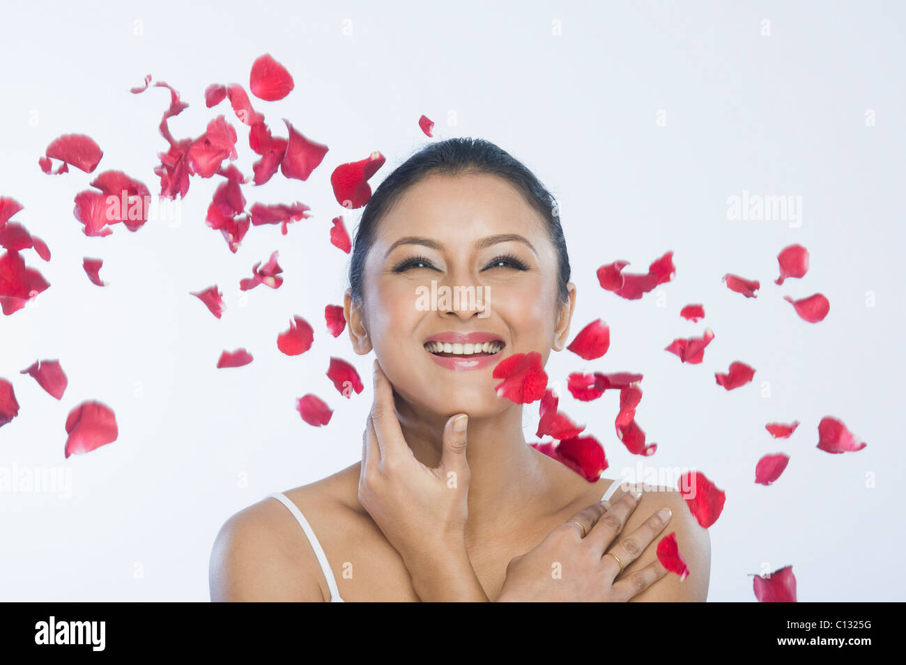 Rose petals falling on a woman - Stock Image