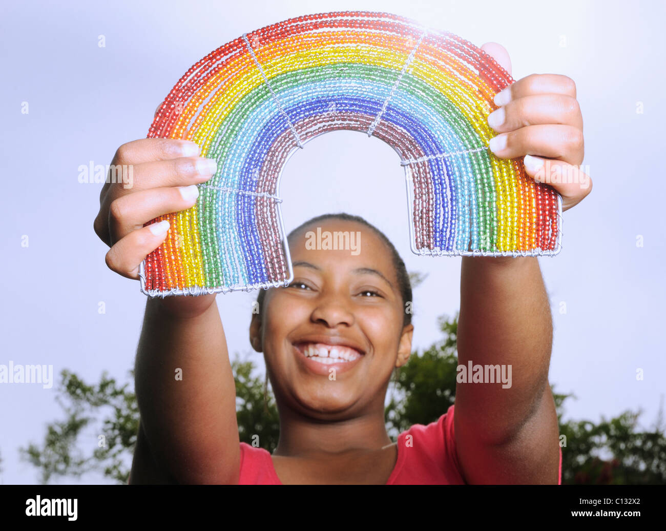 Teenage girl holding up a beaded rainbow. Cape Town, South Africa - Stock Image