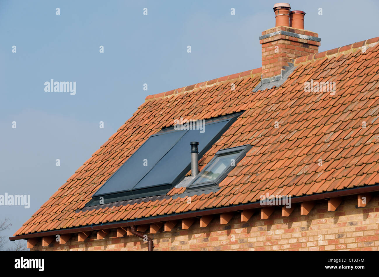 Integrated thermal solar panel on the roof of a newly built house to produce hot water - Stock Image