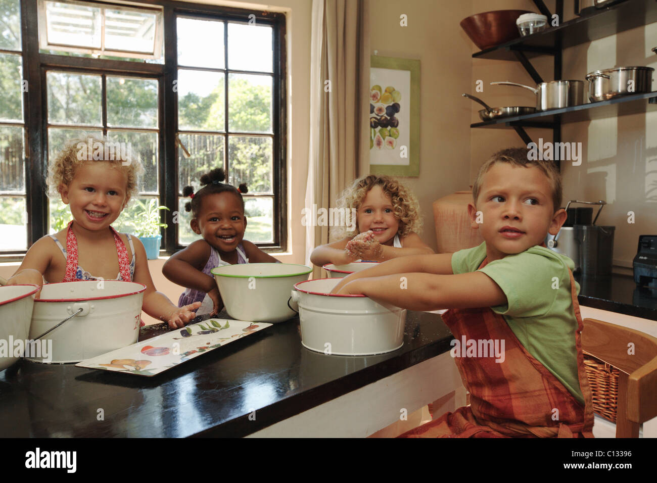 Boys and girls (4-5, 2-3, 18-23 months) making food around table, Cape Town, Western Cape Province, South Africa - Stock Image