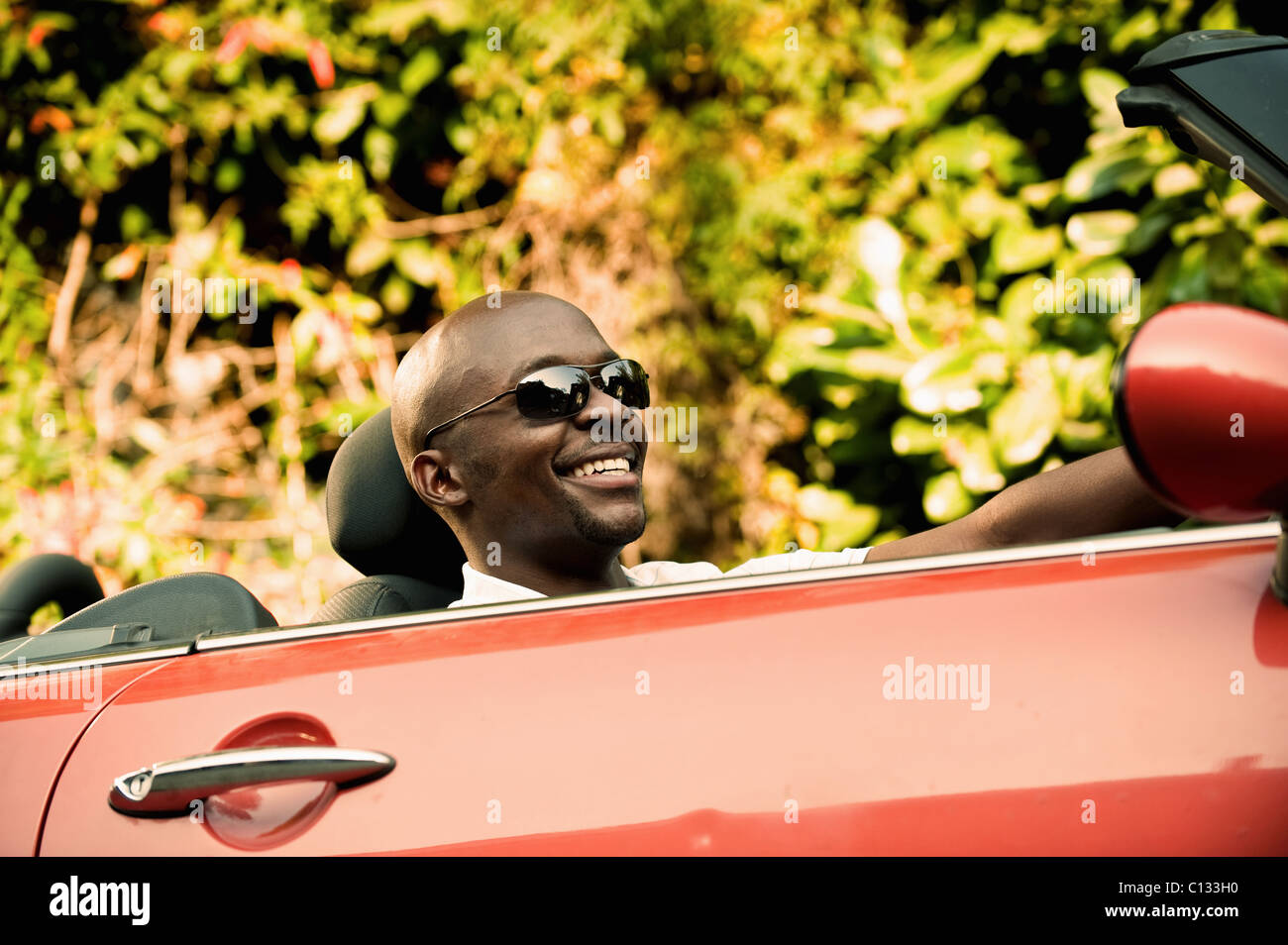 Young man smiling as he drives convertible car. Johannesburg, South Africa - Stock Image