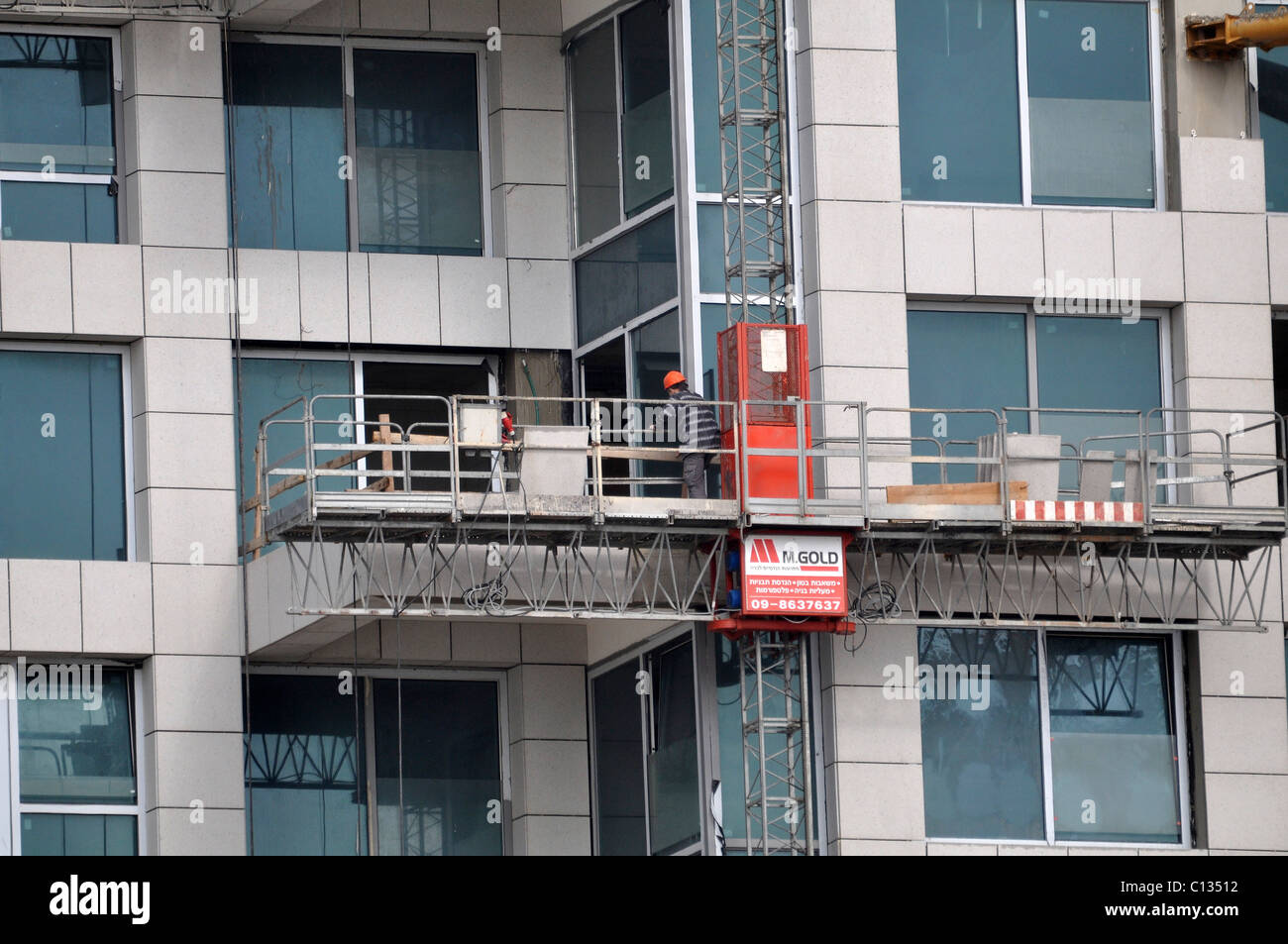 Israel, Tel Aviv Scaffold lift on the side of a highrise building - Stock Image