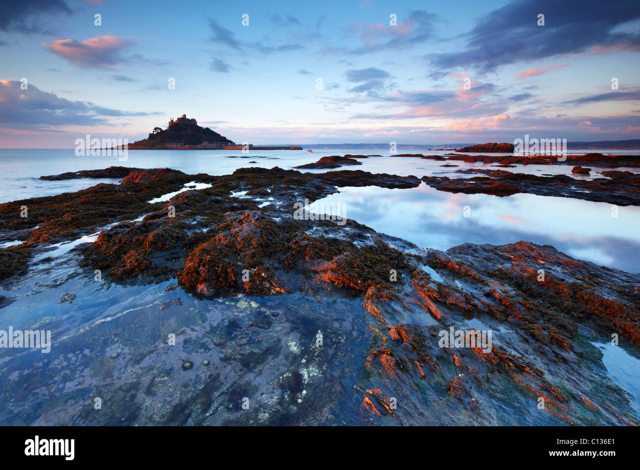 St Michael's Mount lit by the glow of the morning sun. The retreating tide creates rock pools that reflect the dawn Stock Photo