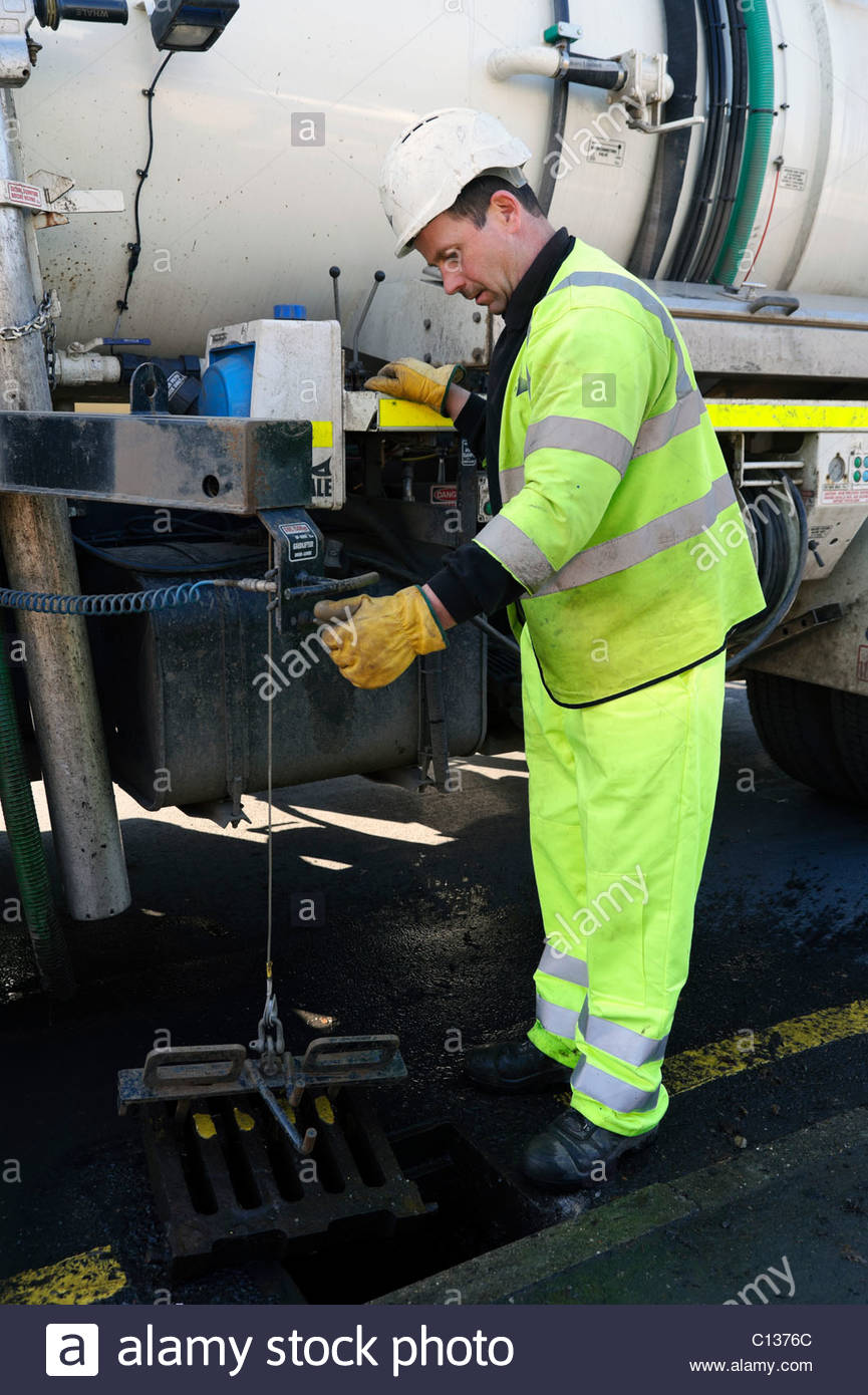 Workman wearing hi-viz protective safety gear, cleaning drains with a sludge gulper tanker lorry. Gully drain clearing - Stock Image