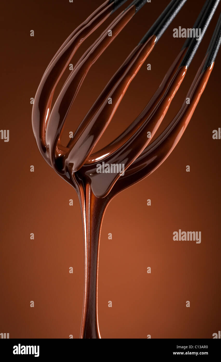 melting chocolate dripping from a whisk - Stock Image