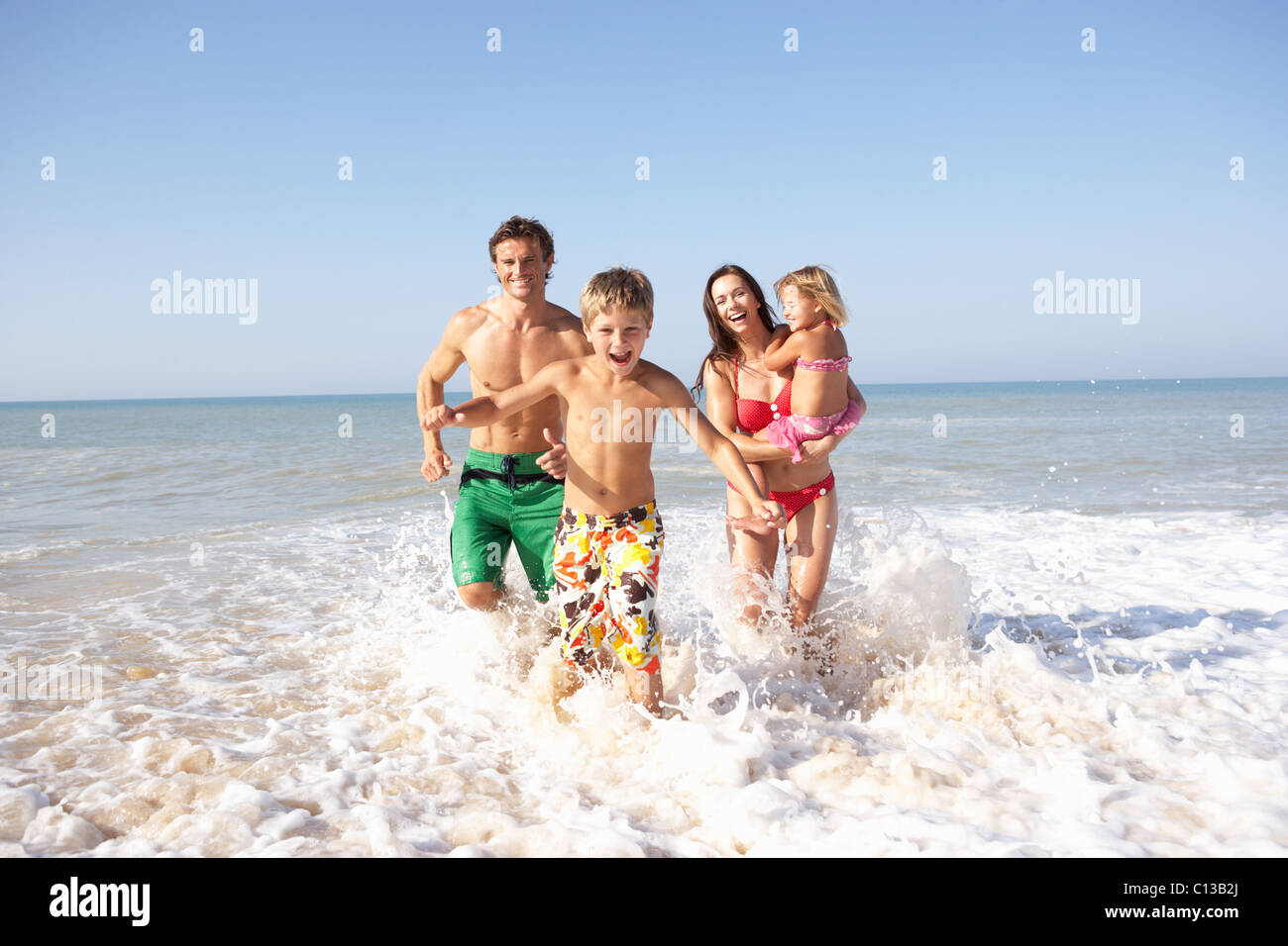 Young family play on beach - Stock Image