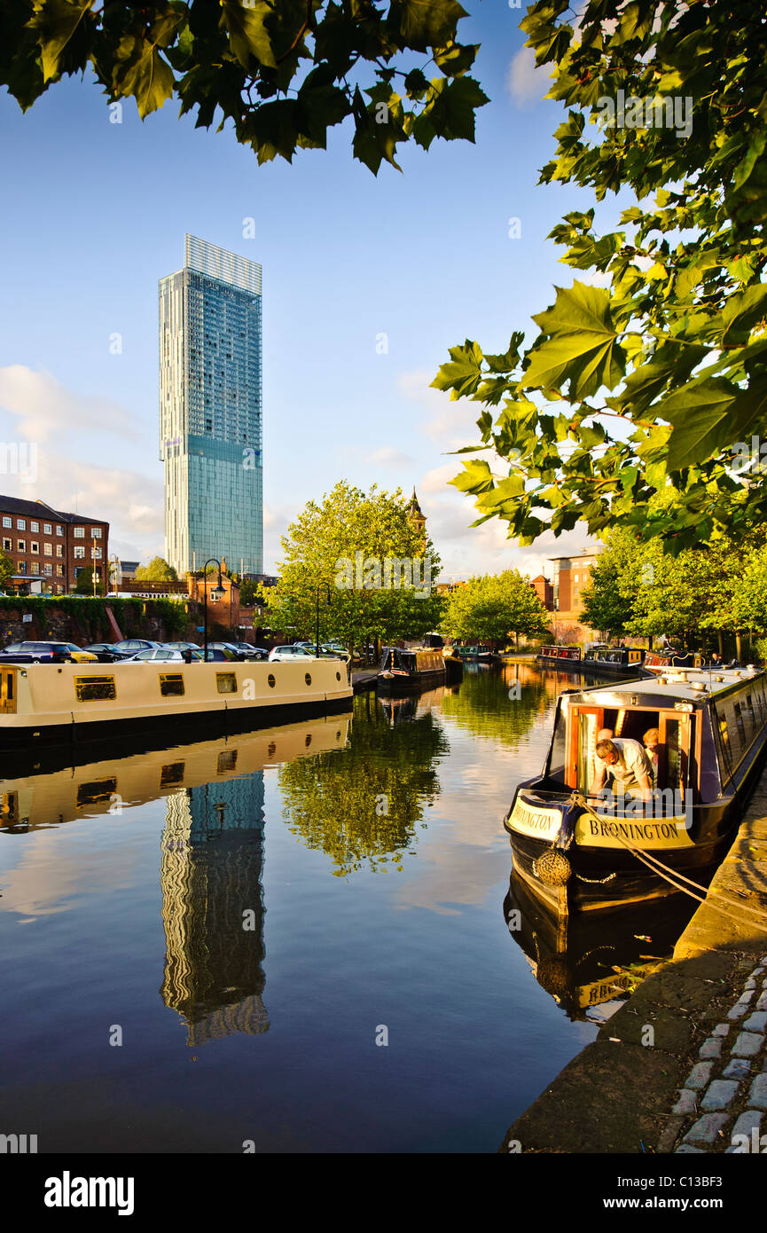 Castlefield canal area Manchester. Bright sunny day with canal and barge in the foreground  Beetham Hilton hotel - Stock Image