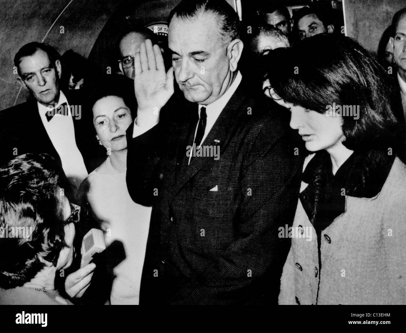 LADYBIRD JOHNSON watches as husband LYNDON B. JOHNSON gets sworn in as President while former First Lady JACQUELINE Stock Photo