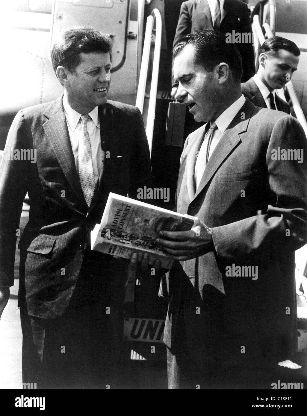JOHN F. KENNEDY and Vice President RICHARD M. NIXON discuss the best seller ADVISE AND CONSENT Stock Photo