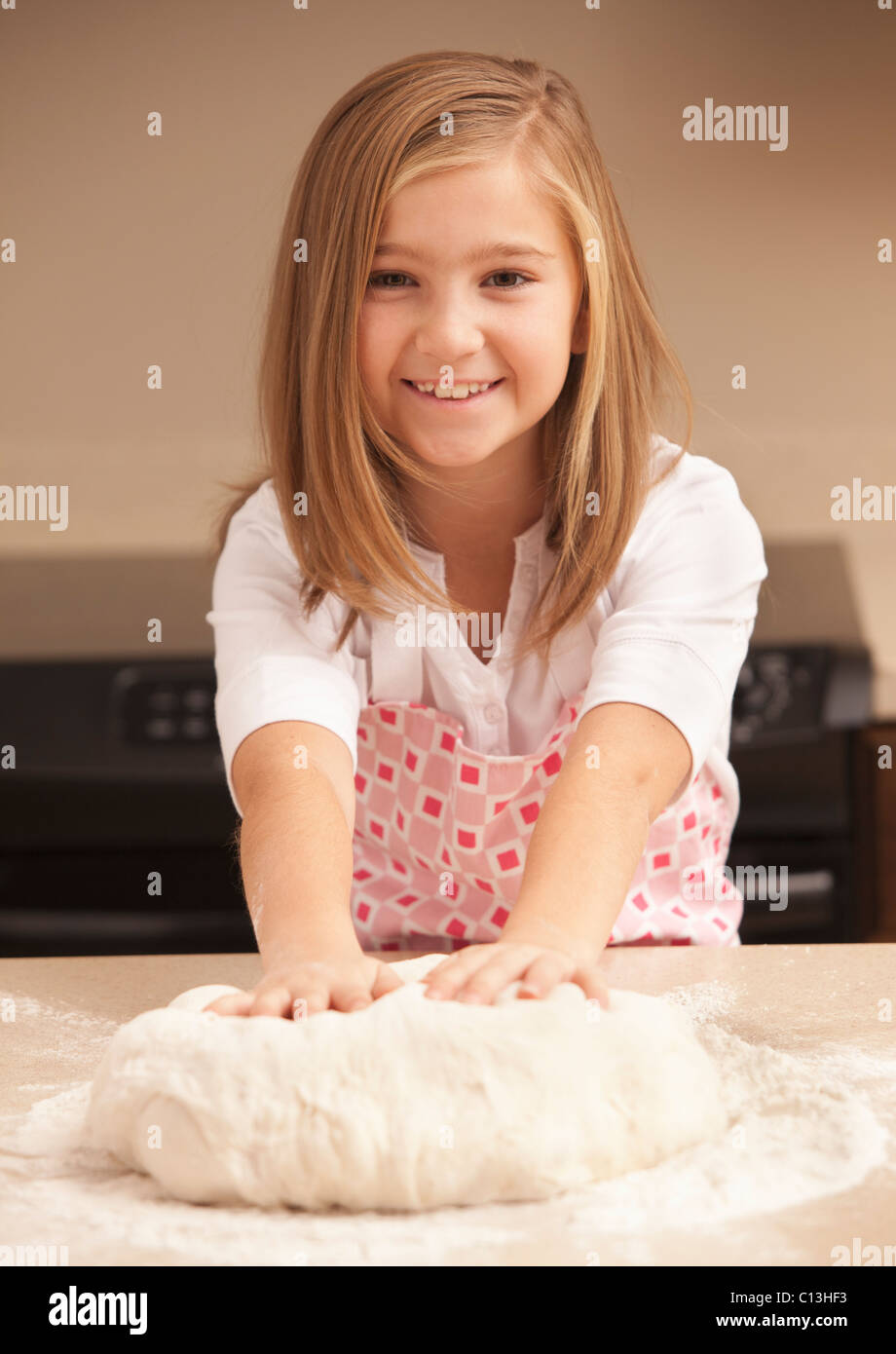 USA, Utah, Lehi, Portrait of girl (10-11) kneading dough in kitchen - Stock Image