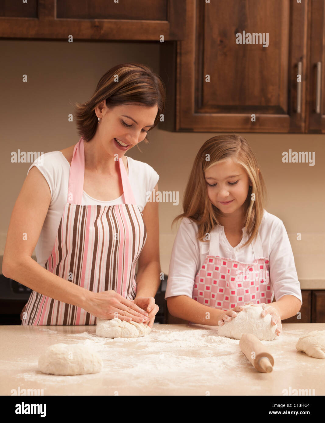 USA, Utah, Lehi, Mother and daughter (10-11) kneading dough in kitchen - Stock Image