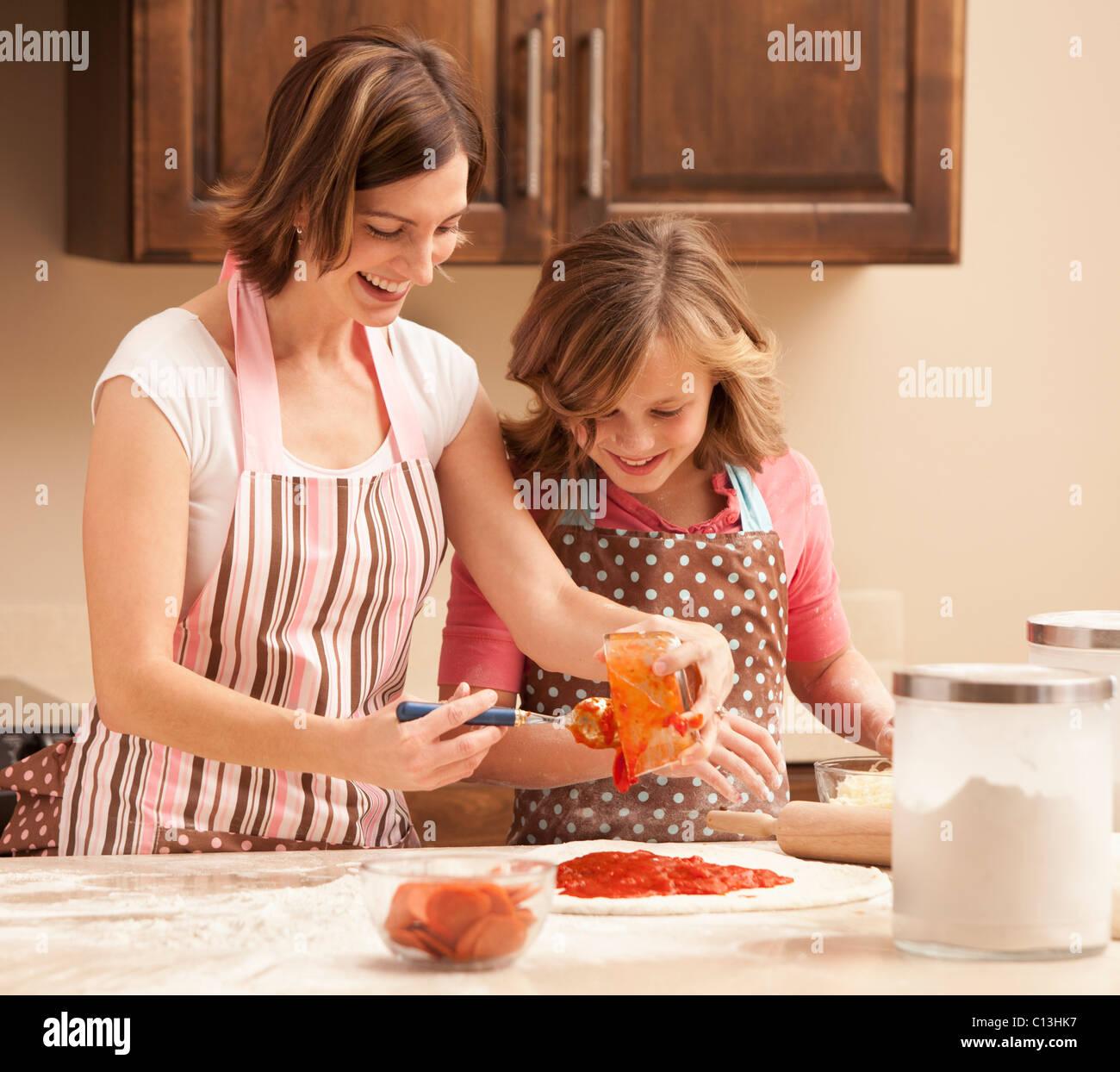 USA, Utah, Lehi, Mother and daughter (10-11) preparing pizza in kitchen - Stock Image