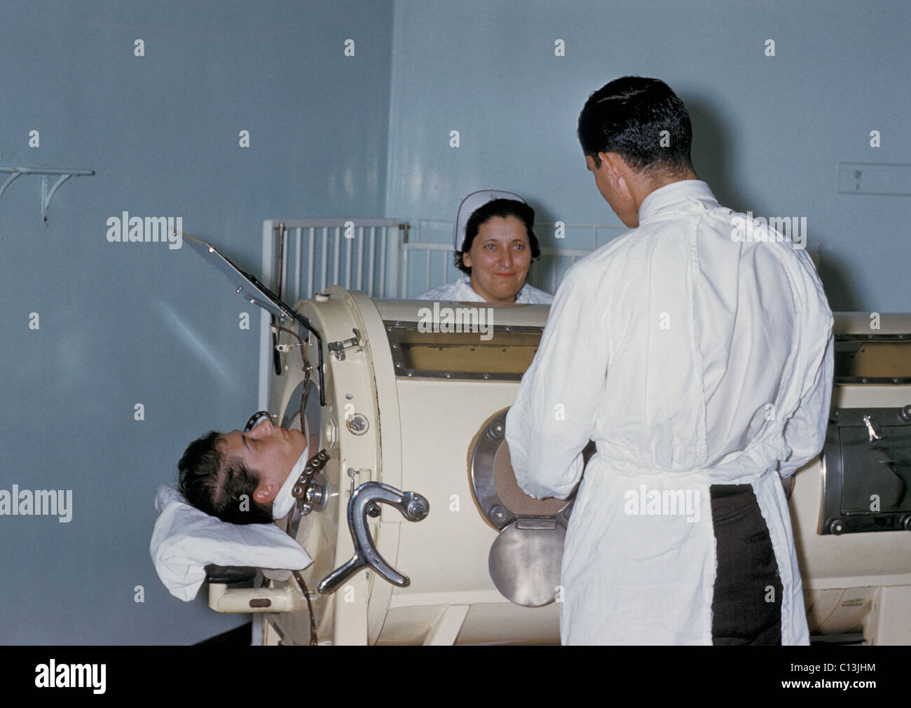 Hospital staff are examining a patient in a tank respirator, iron lung, during a Rhode Island polio epidemic. The - Stock Image