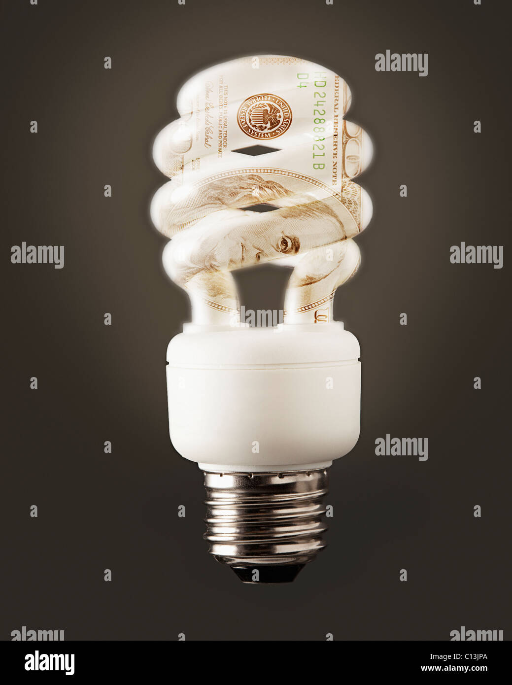 Composition of energy efficient bulb and one hundred dollar note - Stock Image