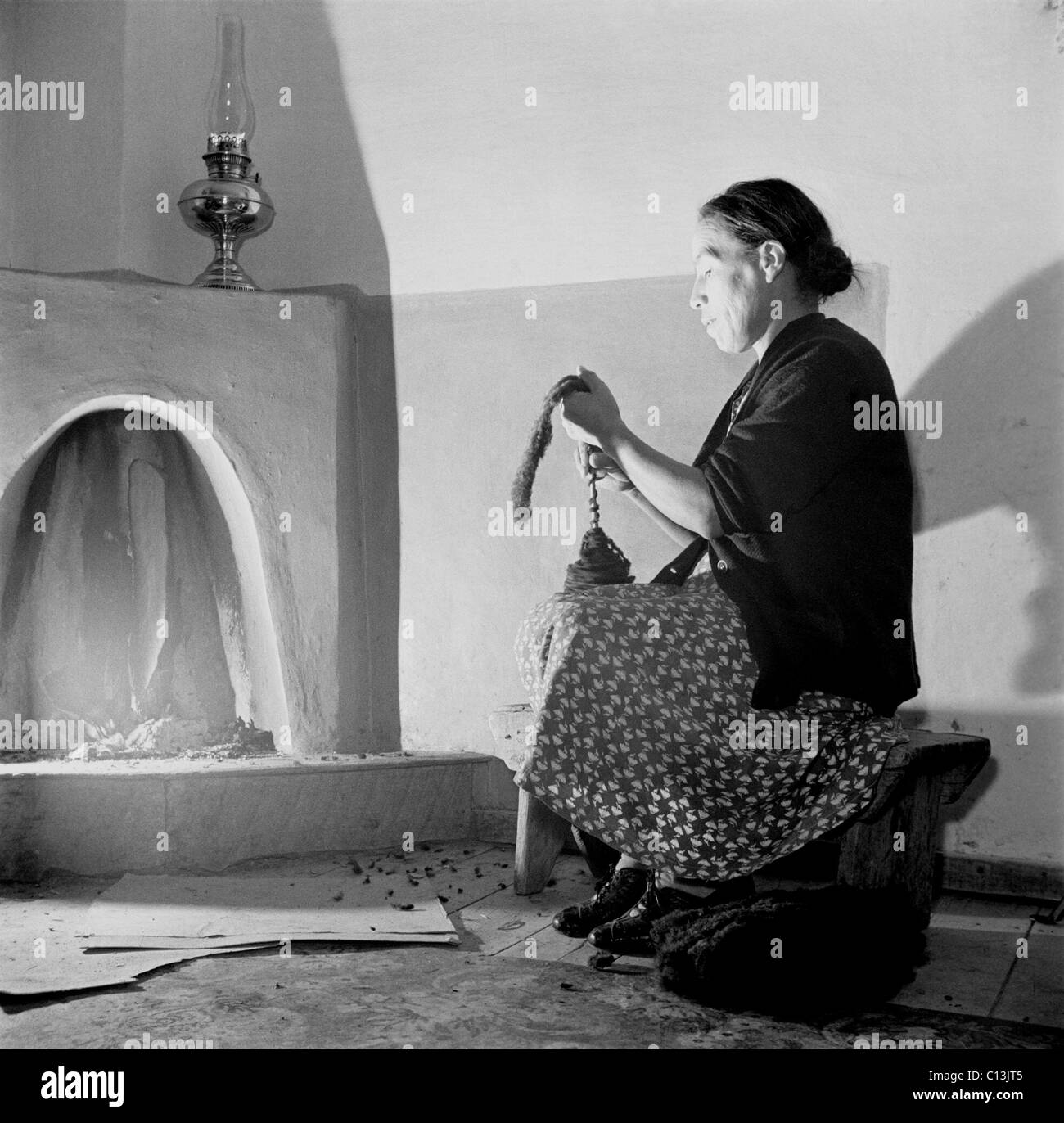 Spanish-American women, Maclovia Lopez, hand spinning wool by the light of the fire in New Mexico's Taos County. - Stock Image