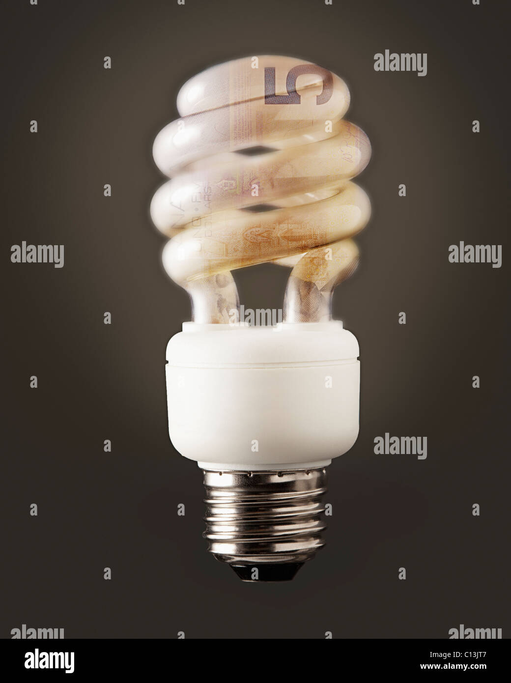 Composition of energy efficient bulb and five canadian dollar banknote - Stock Image