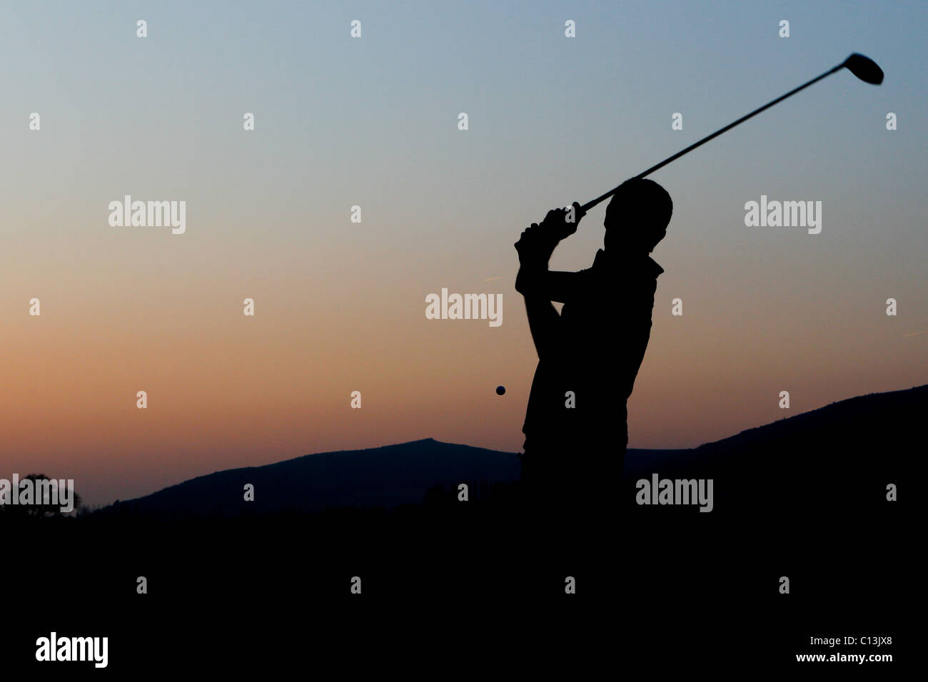 Man playing golf with a scenic landscape surrounding him as the sun sets - Stock Image