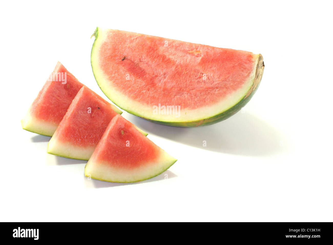 Watermelon quartered with individual slices on white background - Stock Image