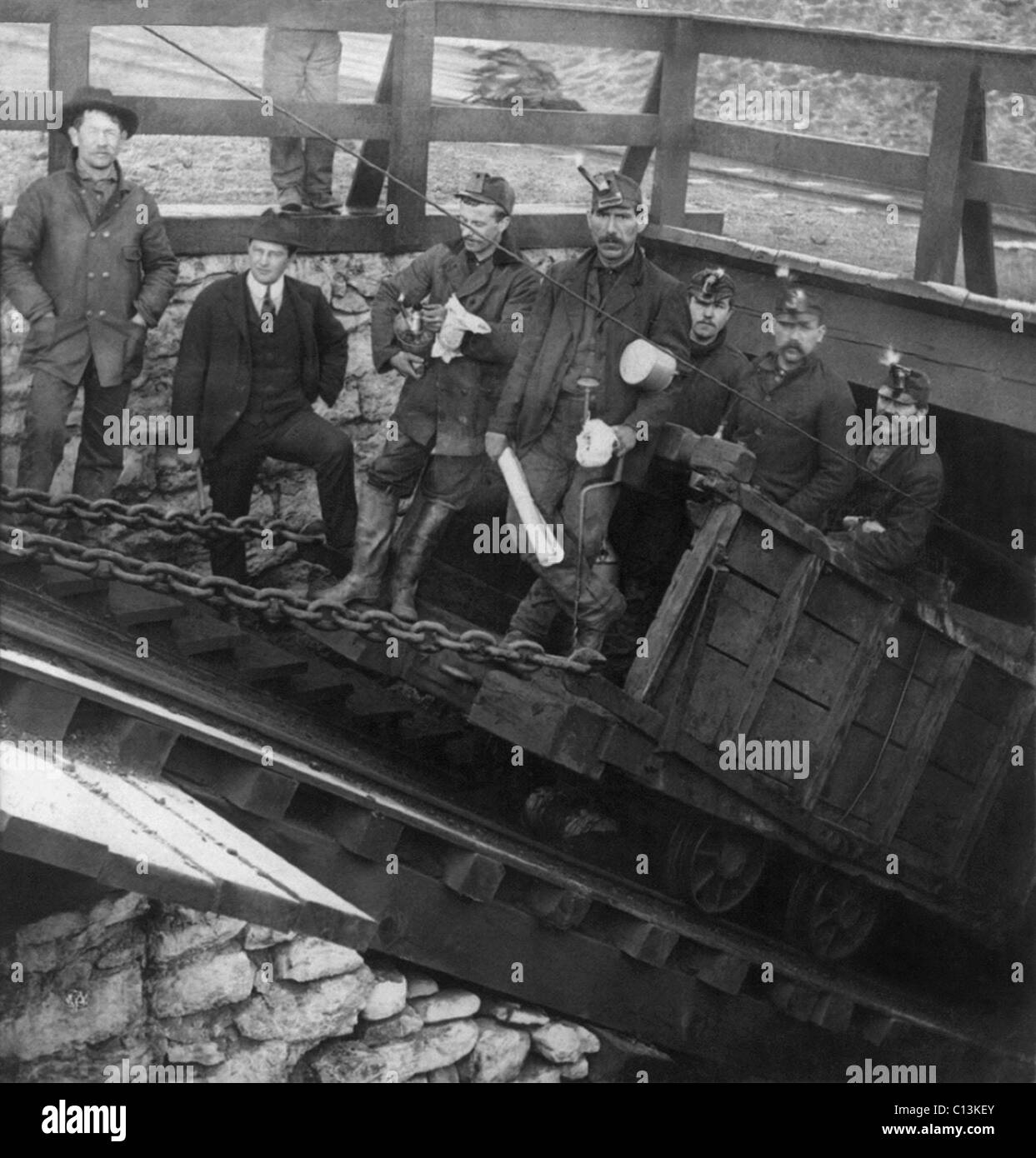 Five miners going into the Slope, descending into coal mine, Hazelton, Pennsylvania. Note the man in a suit, standing - Stock Image