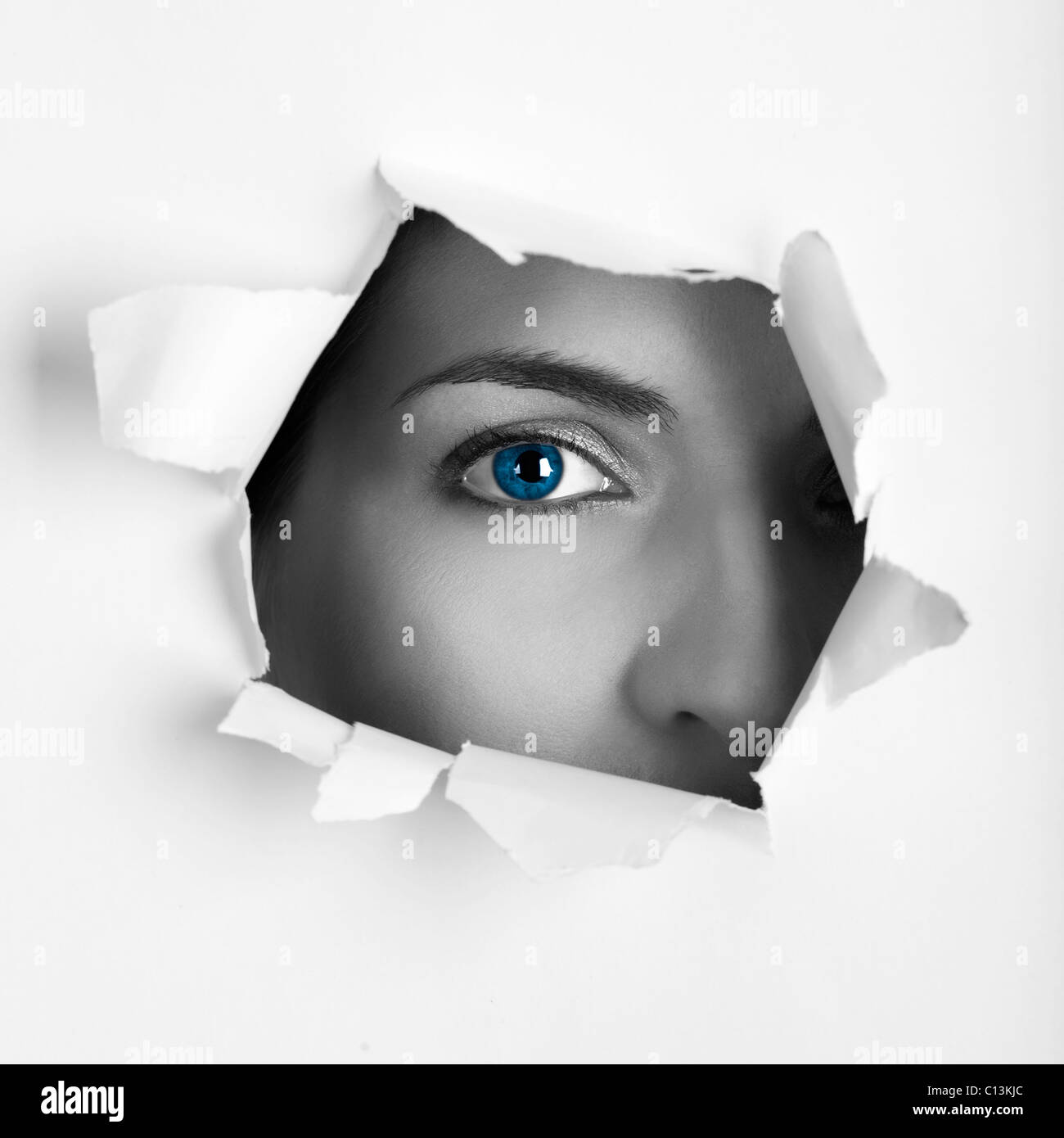 Beautiful female blue eye looking through a hole on a sheet of paper Stock Photo