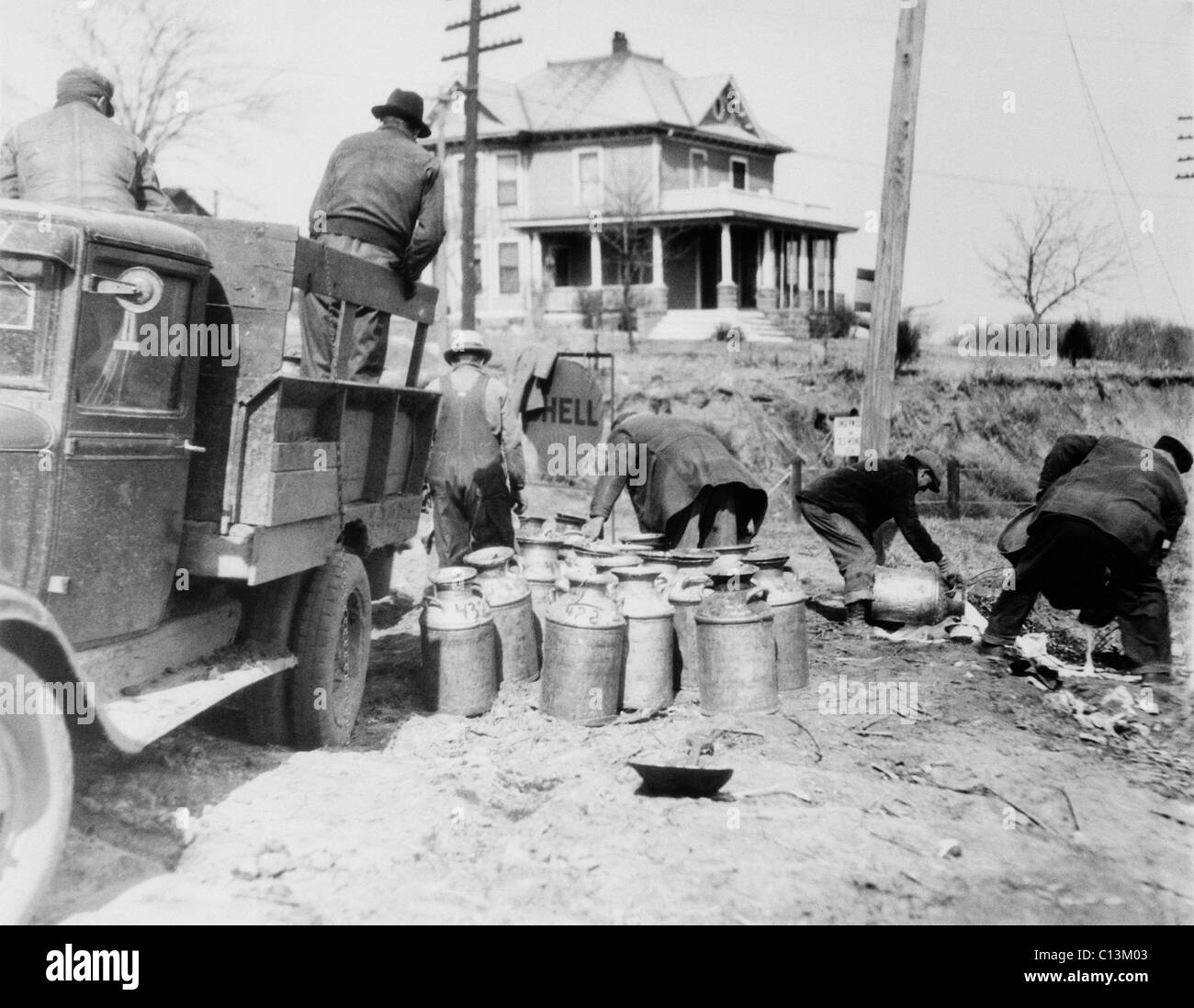 Striking farmers dump milk cans from a truck they have stopped to prevent delivery to market during the Great Depression. - Stock Image