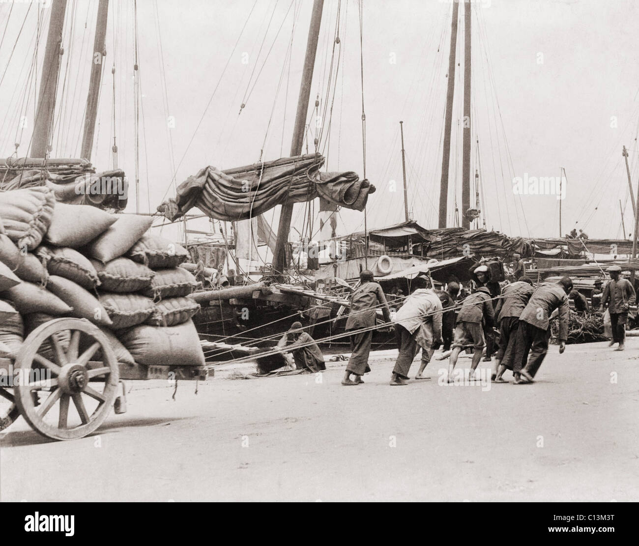 Gang of five Chinese dock workers lean hard on ropes to haul a heavy wagon load of sacks on the Hong Kong waterfront. - Stock Image