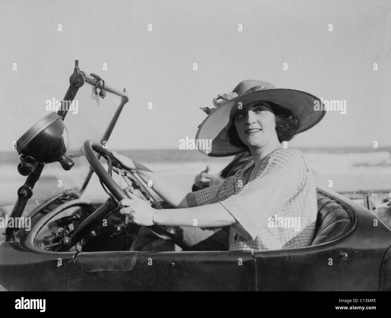 Young woman at steering wheel of automobile. 1921. LC-USZ62-100382 - Stock Image
