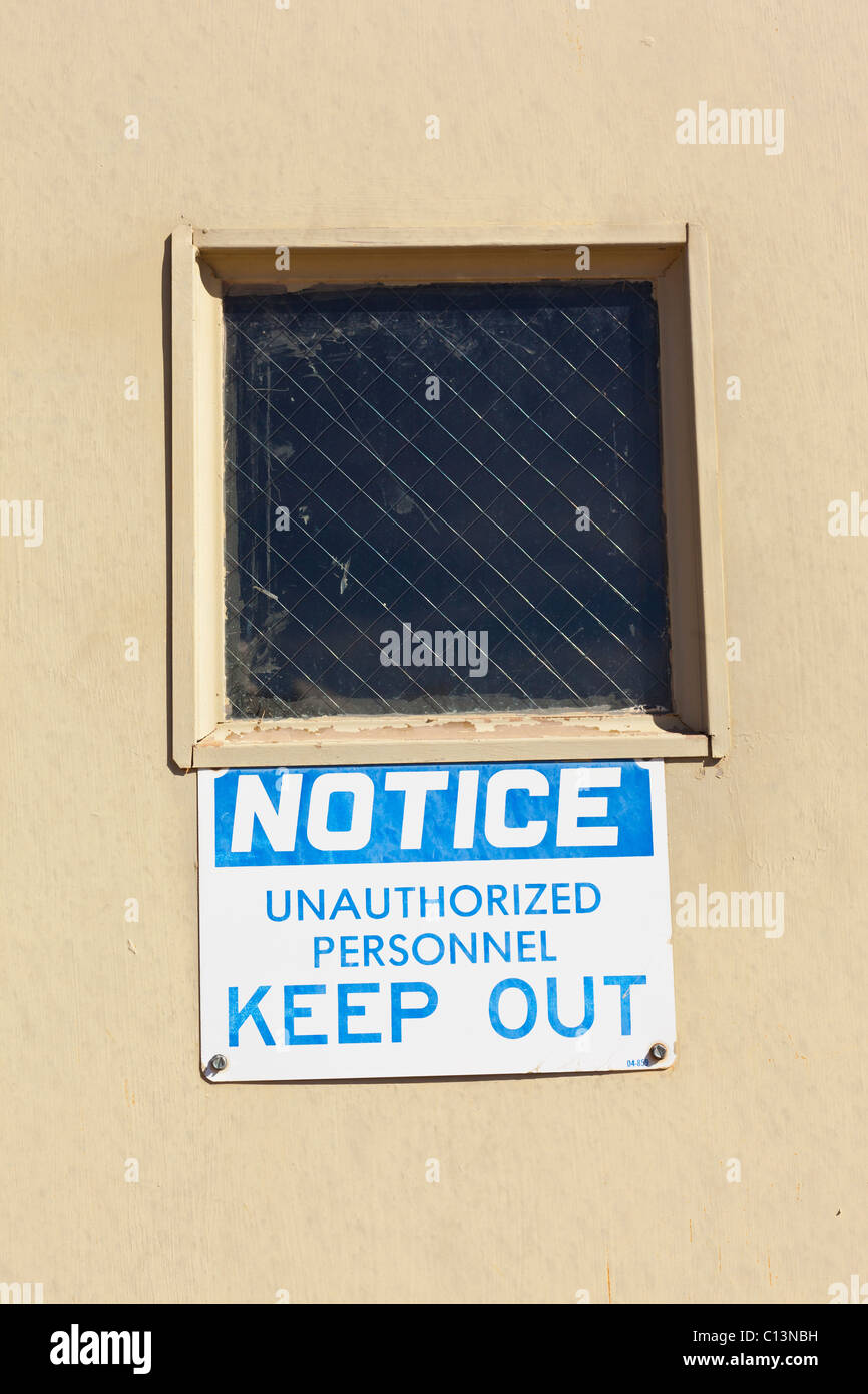 A sign posted on a door underneath a wire meshed window that reads: Notice Unauthorized Personnel Keep Out. - Stock Image