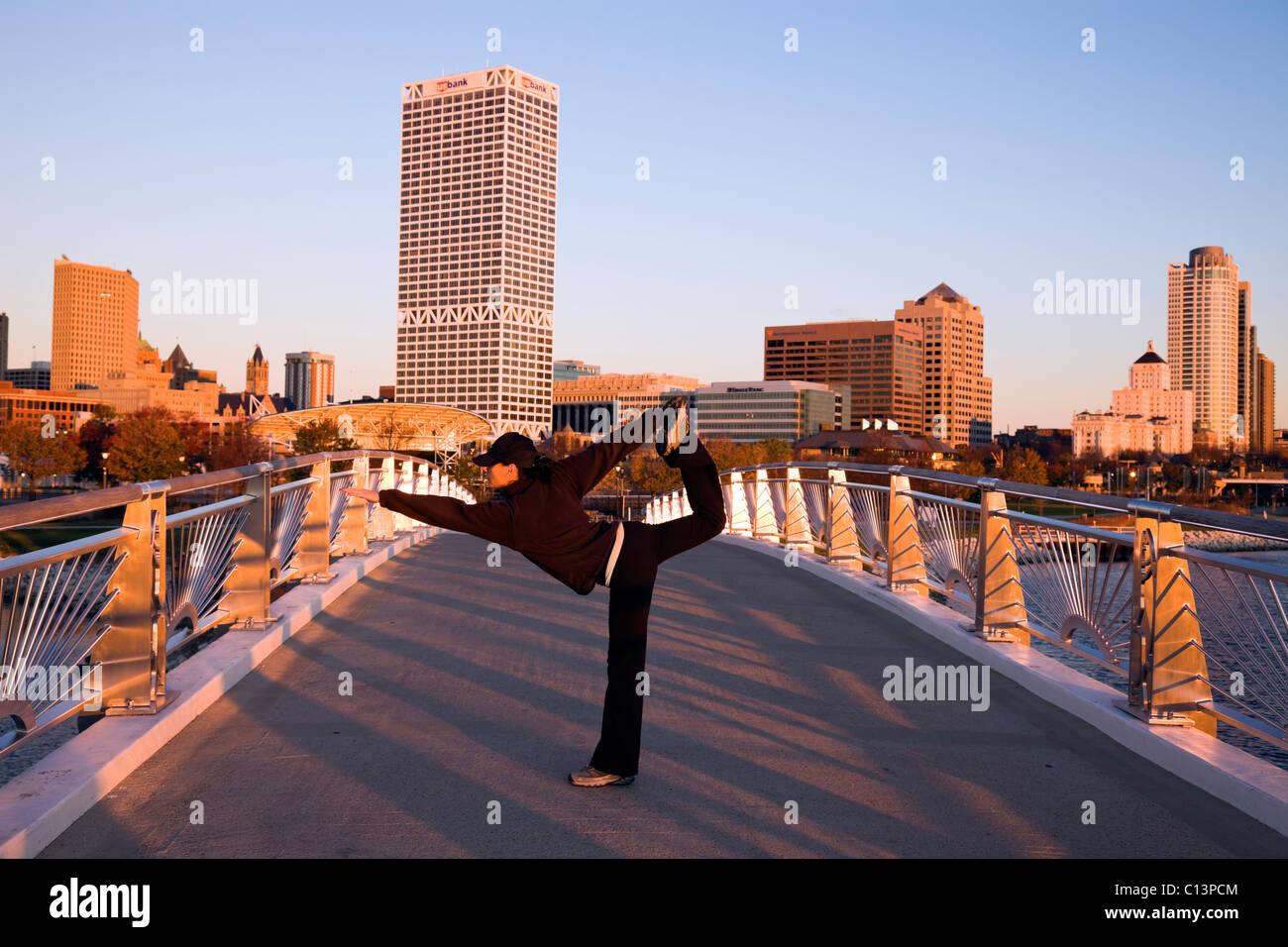 USA, Wisconsin, Milwaukee, Woman doing yoga on bridge in city Stock Photo