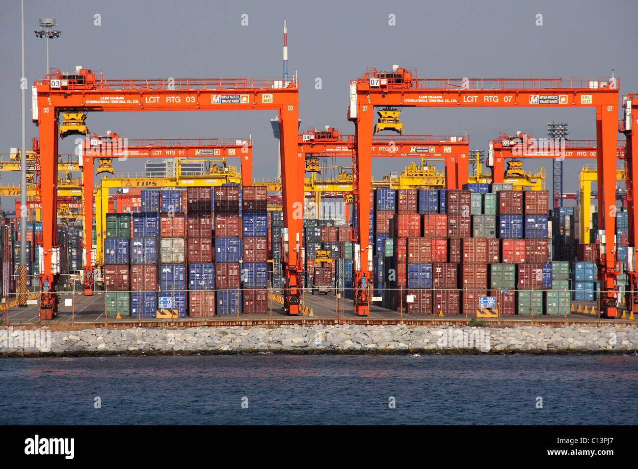 a stack of shipping cargo containers and cranes in a container terminal Stock Photo