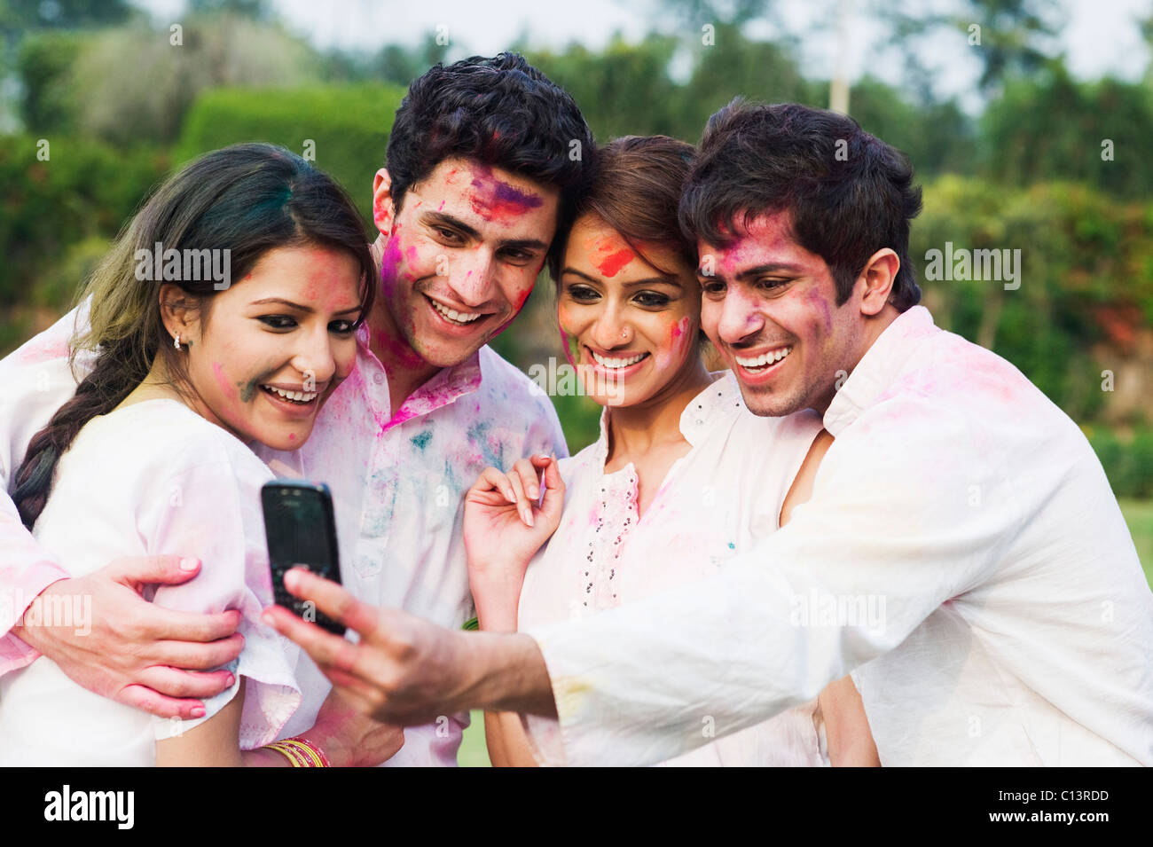 Friends taking a picture of themselves with a mobile phone on Holi Stock Photo