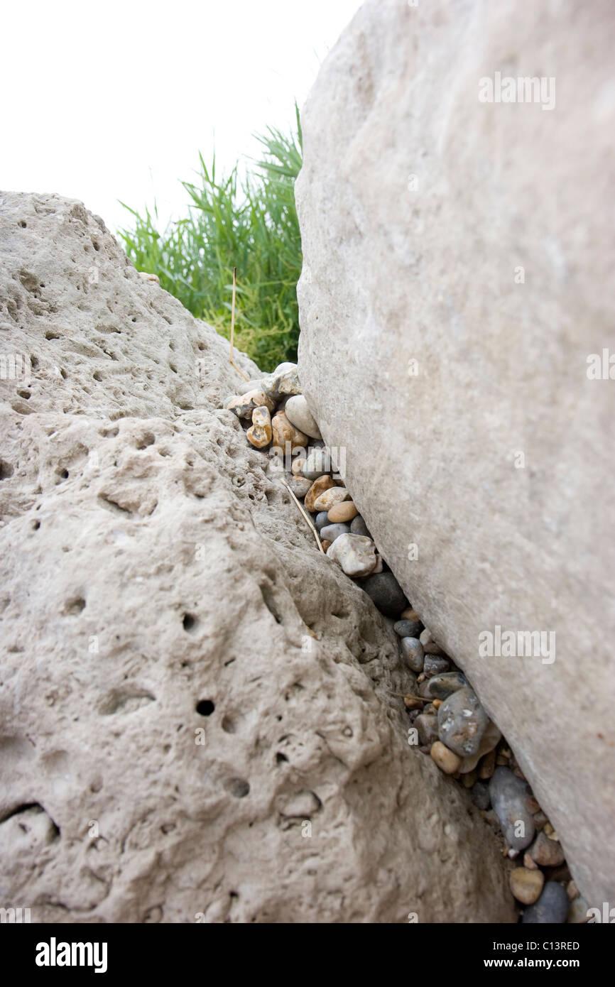 pebble jammed between huge white chalk boulders on the Dorset coast - Stock Image