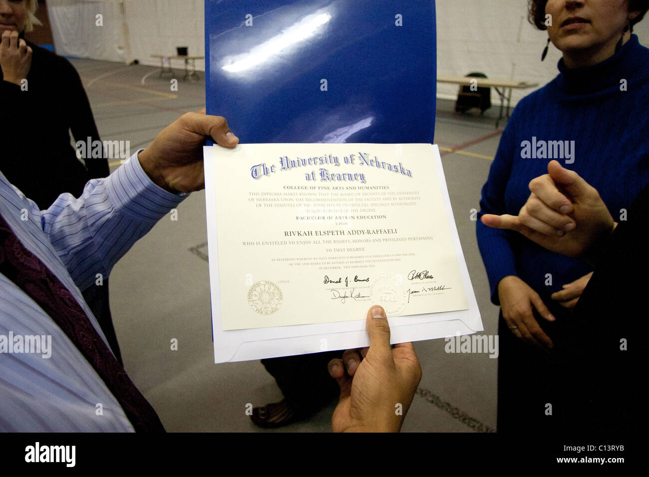 A man holds a college diploma for the University of Nebraska at Kearney. Stock Photo