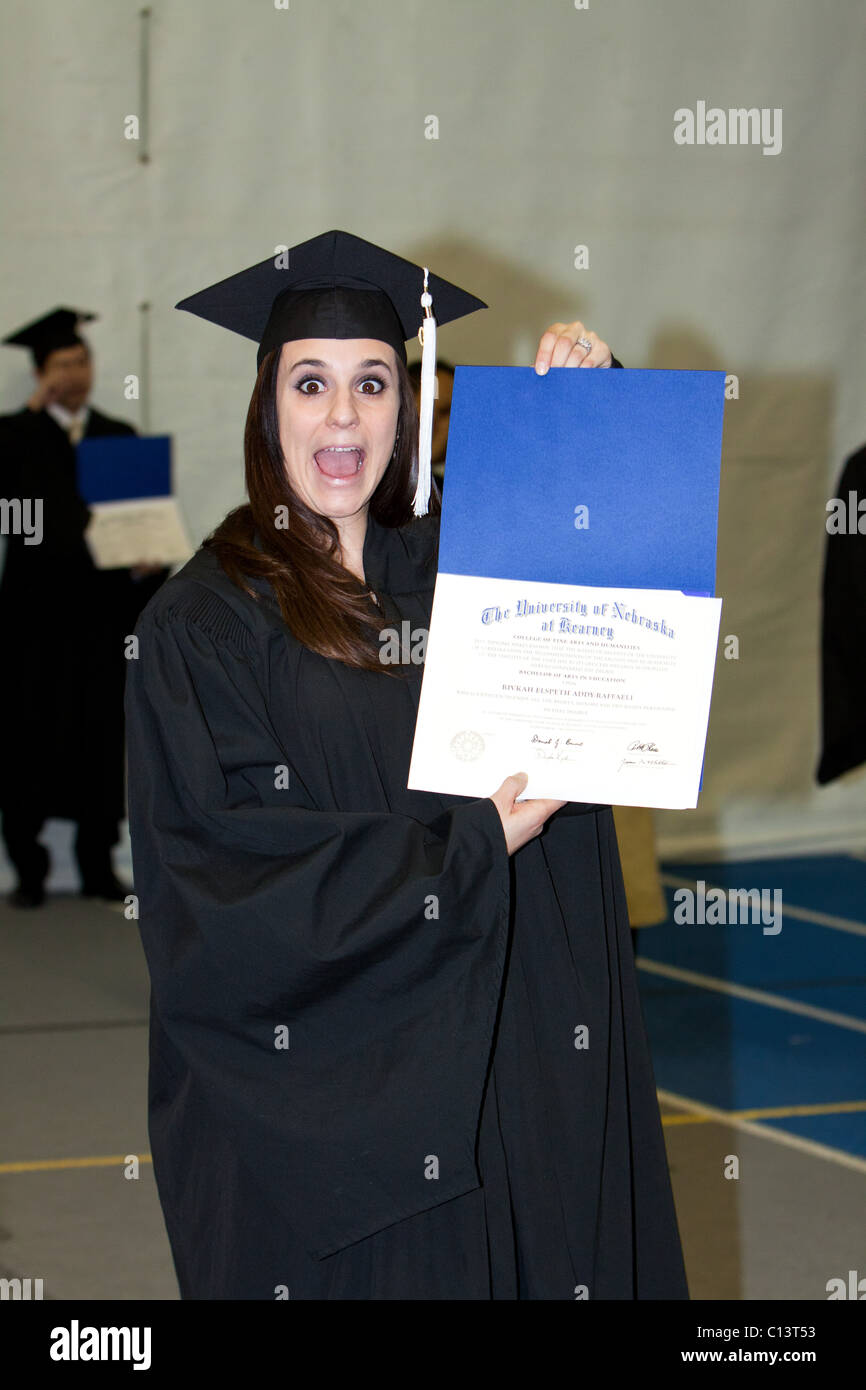 A woman holds her university diploma just after graduating. - Stock Image