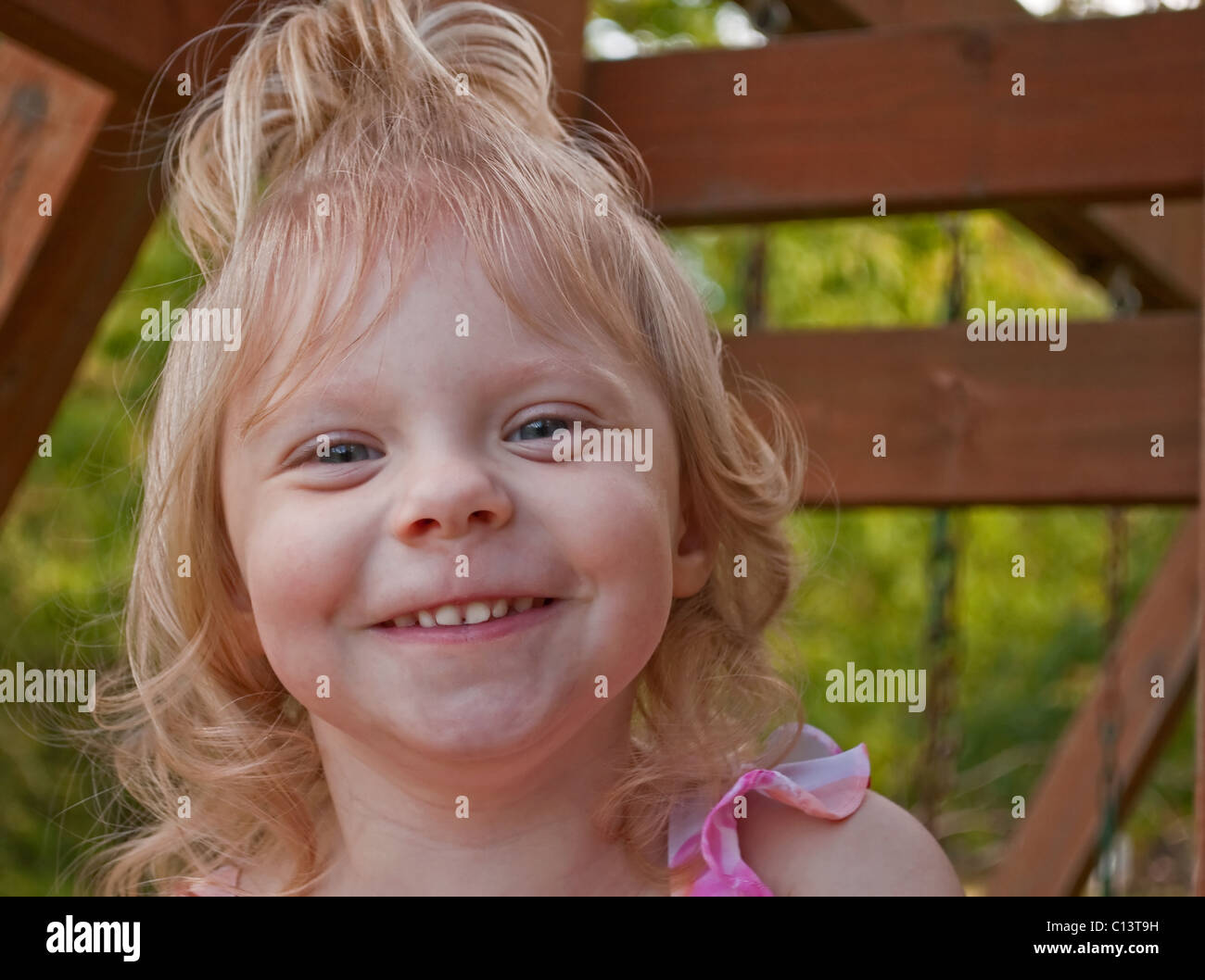 This cute 2 year old Caucasian girl with blond hair, and a pony tail on top  of her head is smiling and happy while being outdoor