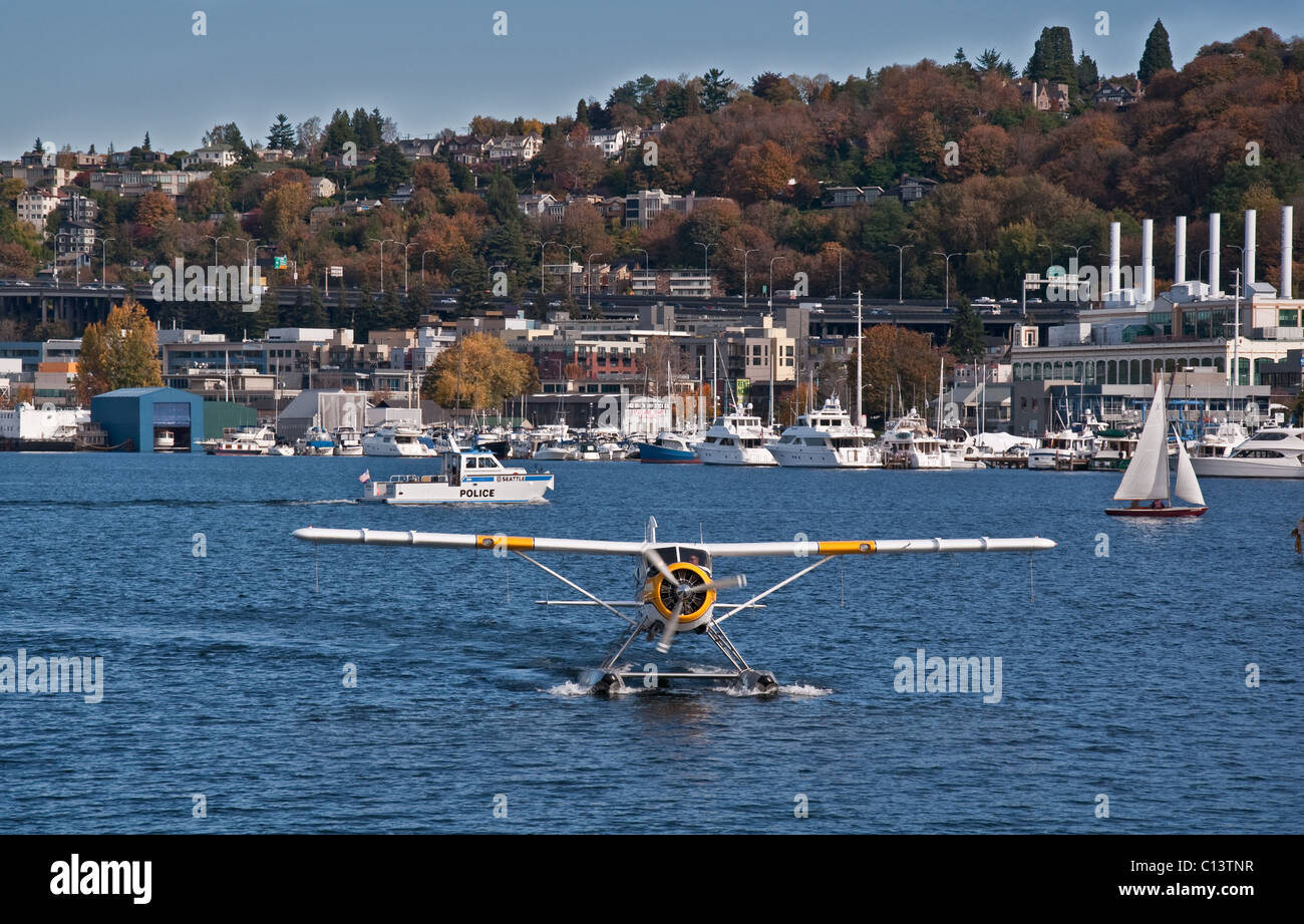 This stock image has a plane and a Seattle police boat traveling on Lake Union, in Seattle, King County Washington - Stock Image