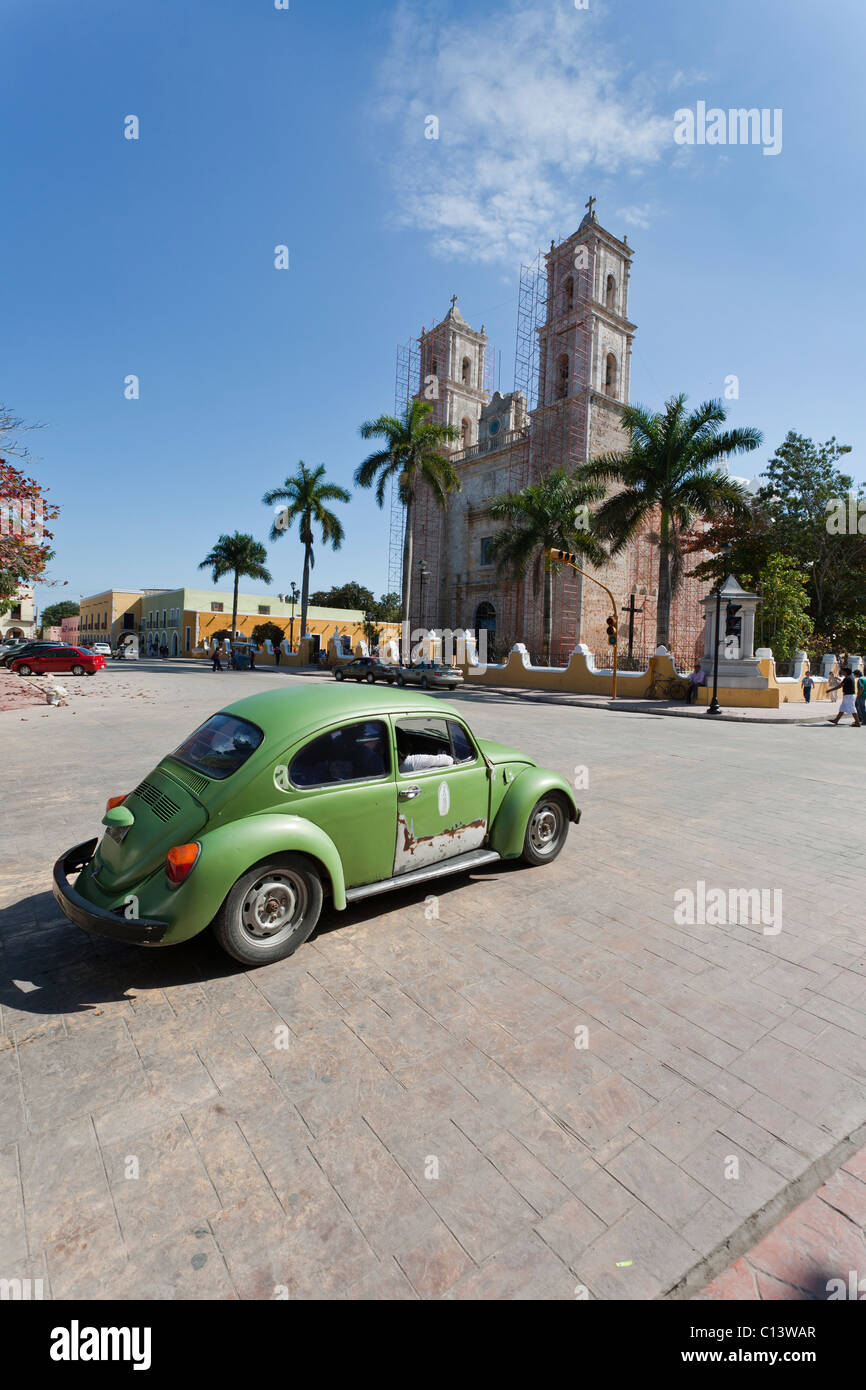 Green VW and the Cathedral. A green VW beetle turns into the square surrounding Valladolid's main church. - Stock Image