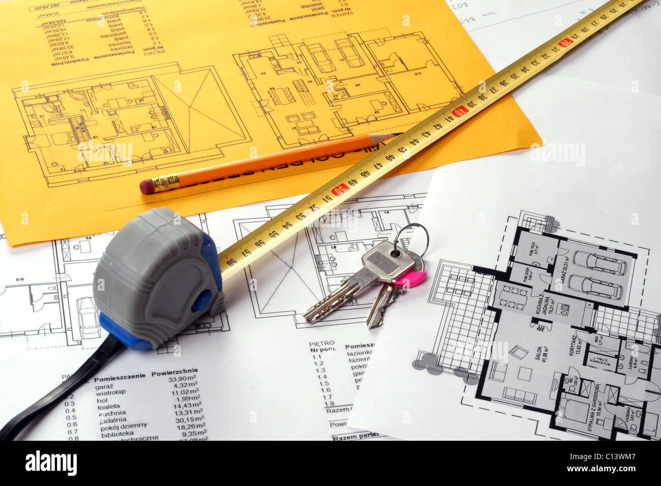 Tools on Blueprints including measuring tape, keys and pencil. House plans printed on white and yellow paper - Stock Image