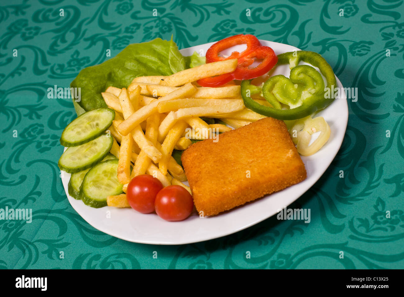 Fried breaded cheese steak with french fries and vegetable - Stock Image