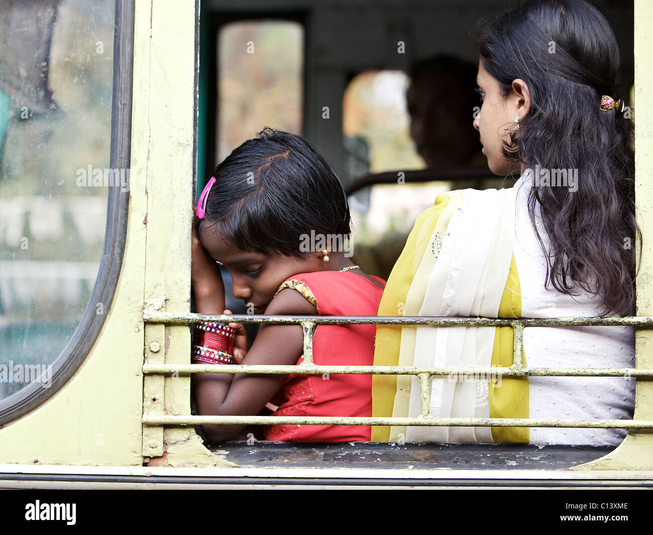 Child asleep on bus, south of Kochi, Kerala, India - Stock Image