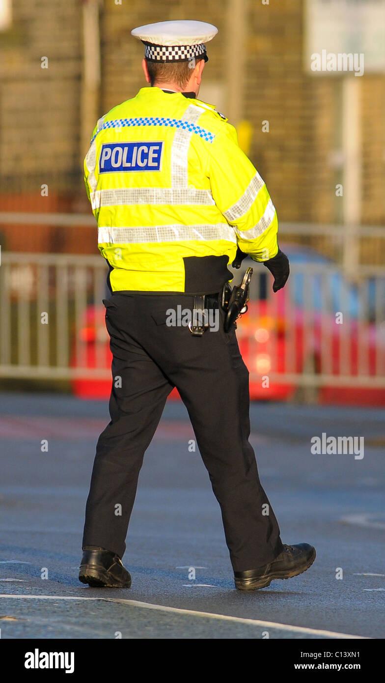 Policeman walks across the road Stock Photo