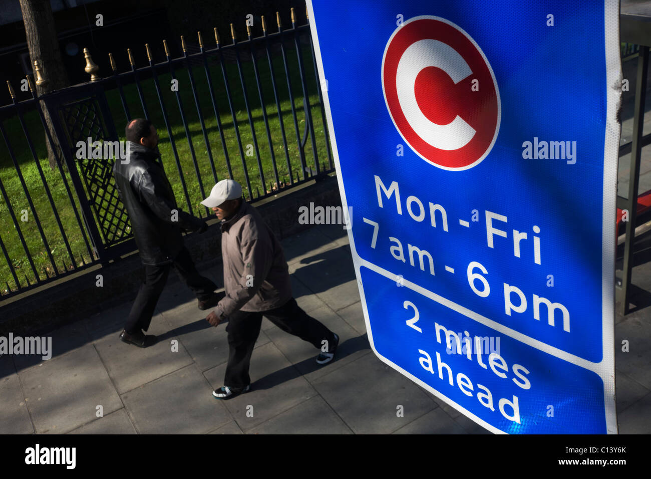 Two pedestrians walk beneath a motorists' Congestion Zone sign on a London street. - Stock Image