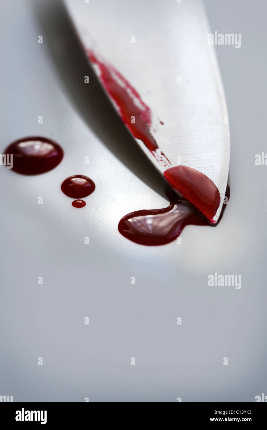 blade of a knife on a white surface with drops of blood - Stock Image