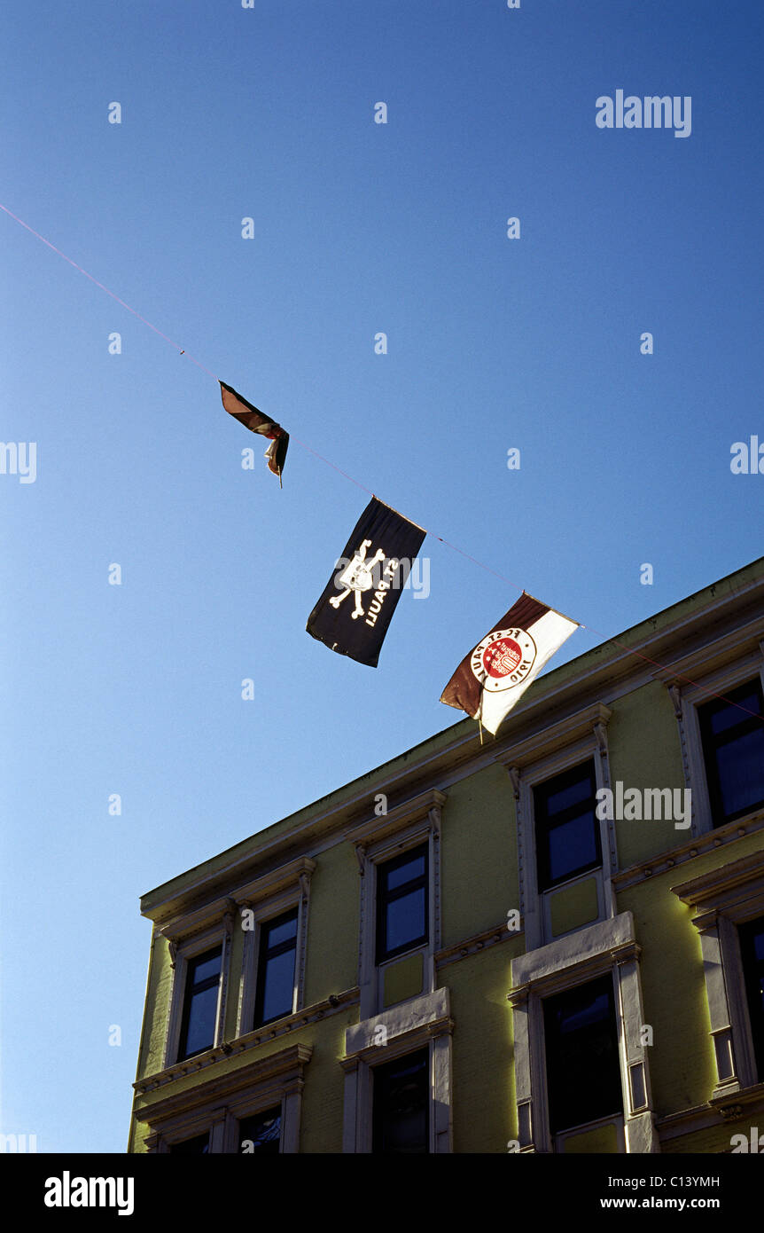 Flags of FC Sankt Pauli football club suspended from a rope between two apartment buildings in Sankt Pauli district - Stock Image