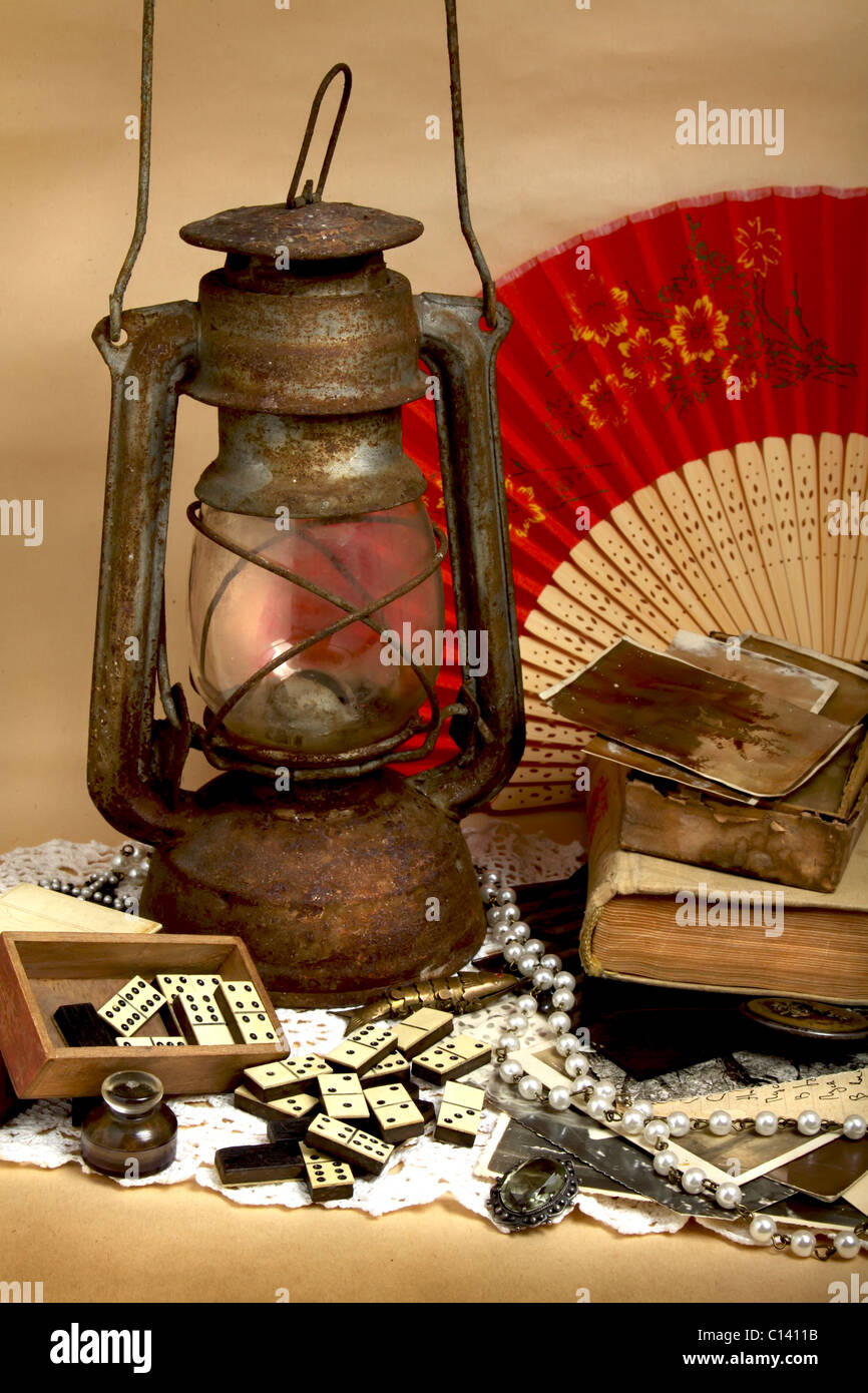 Still life - oil lamp, old photos, antique domino and jewelry - Stock Image