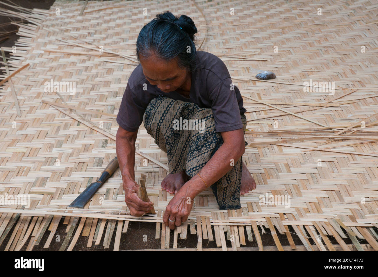 Woman weaving split bamboo into traditional panels for lining the walls and ceiling of traditional Balinese houses - Stock Image