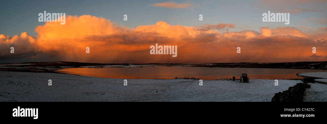 A bank of cumulus shower clouds at sunset, over the Loch of Yarrows, Caithness, Scotland, UK Stock Photo