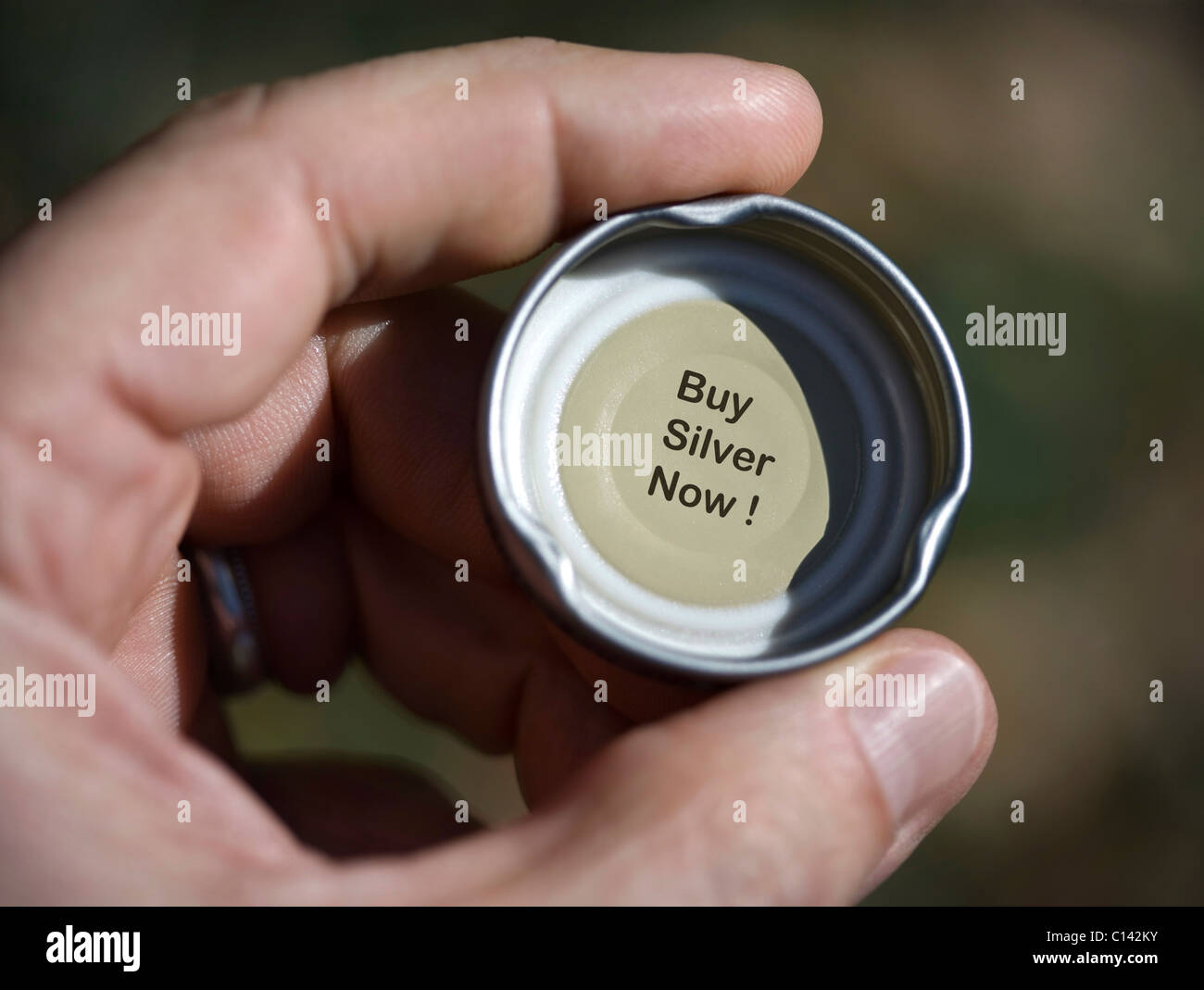 Inside of a bottle cap with message to buy silver now. - Stock Image